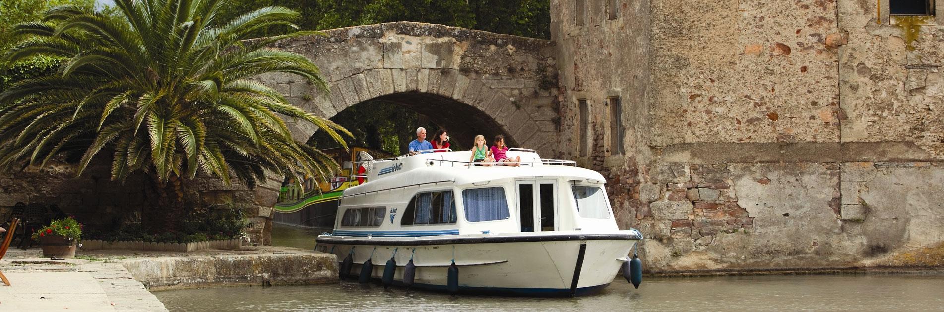 Flodbåde passerer under bro på Canal du Midi